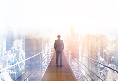 business risk: Business risk and research concept with back view of businessman standing on suspended bridge above New York city and looking into the distance. Toned image, 3D Rendering