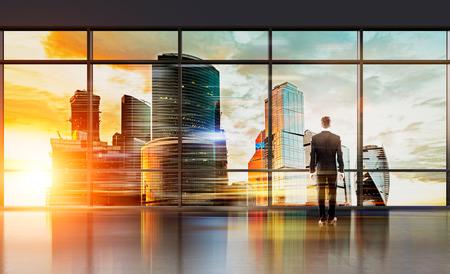 Zakenman in het interieur staan voor enorme panoramische raam te kijken naar de stad met zonlicht. onderzoek concept Stockfoto