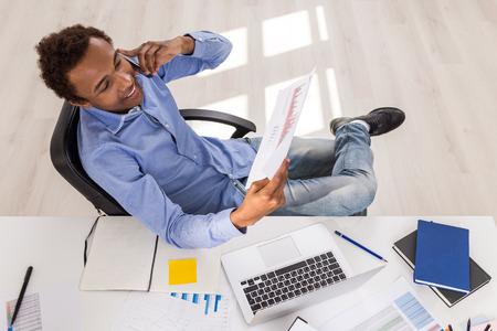 Knappe Afro-Amerikaanse zakenman met zakelijke rapport in de hand praten over de telefoon op het kantoor bureau met laptop en verschillende andere items. Uitzicht van boven Stockfoto