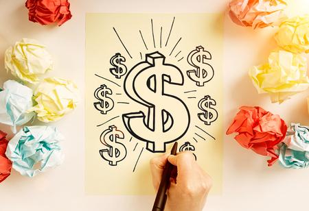 signos de pesos: concepto de crecimiento financiero con signos gráfico de la mano de un dólar en la hoja de papel rodeado de coloridas bolas de papel arrugado Foto de archivo