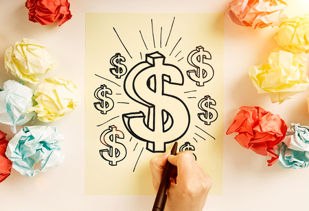 dollar signs: Financial growth concept with hand drawing dollar signs on paper sheet surrounded with colorful crumpled paper balls