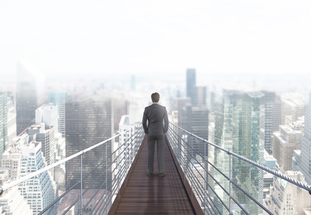 business risk: Business risk and research concept with back view of businessman standing on suspended bridge above New York city and looking into the distance. 3D Rendering