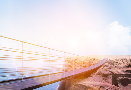 business risk: Business risk and success concept with bridge leading to cliff on sea and bright sky with sunlight background. Toned image. 3D Rendering