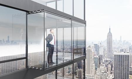 penthouse: Thoughtful businessman looking into the distance from empty balcony interior on New York city background. 3D Rendering Stock Photo