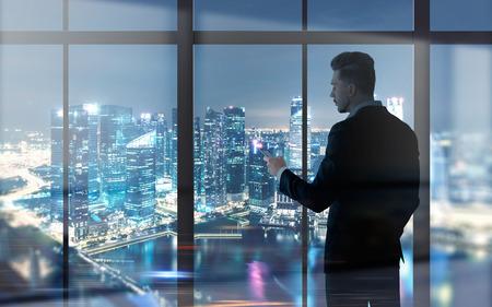 Zijaanzicht van jonge zakenman die cellphone gebruiken tegen panoramisch venster met de verlichte mening van de nachtstad