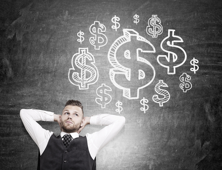 thought cloud: Relaxing businessman daydreaming about money on chalkboard background with dollar sign sketch inside thought cloud. Financial growth concept Stock Photo