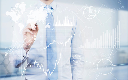 Businessman drawing abstract financial charts and map on light background. Global business concept