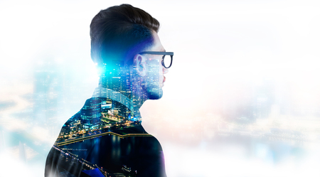 Stylish businessman in glasses on illuminated night Singapore city background with copy space. Double exposure 免版税图像