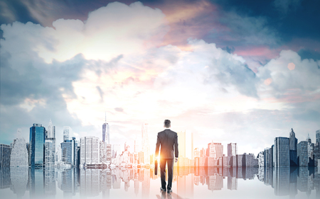 Businessman with briefcase looking at New York city on sky background with clouds and sunlight. Research concept