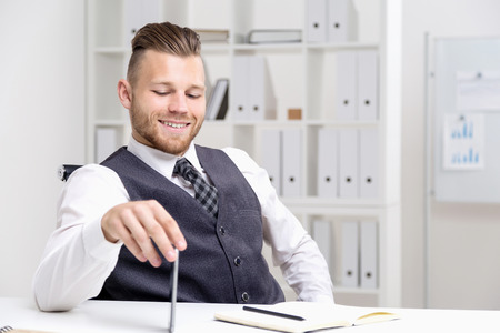 broadly: Young businessman in formal clothes sitting at his desk smiling broadly and looking at his notes. Concept of corporate work
