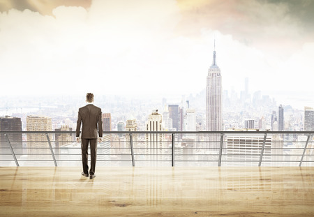 Businessman in suit looking at city of New York thinking and planning right strategy for his project. Concept of decision making.