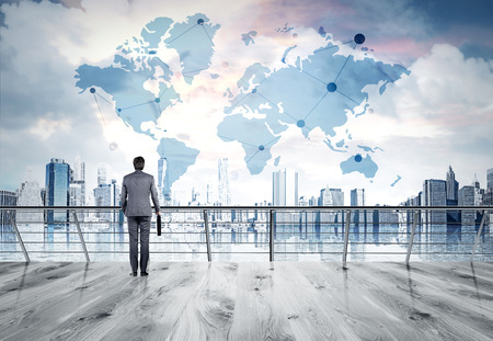 Businessman in suit standing on bridge, looking at New York city thinking about perspectives. Consept of business success. Sketch of world map at background. Elements of this image furnished by NASA. Stock Photo