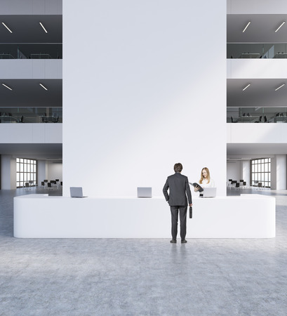 reception table: Reception in modern office. Man and woman in suits standing in front of big white table with computers. Chairs and other rooms in background. Concept of business meeting. 3d rendering. Mock up Stock Photo