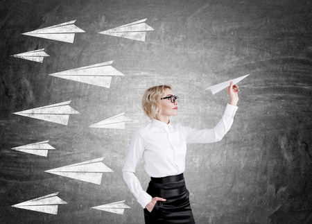Blond woman with glasses is holding paper plane in front of blackboard with sketches of other planes on it. Concept of implementation of idea