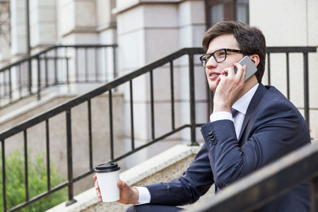 teleworking: Handsome young businessman sitting outside on building stairs, holding coffee cup and talking on phone