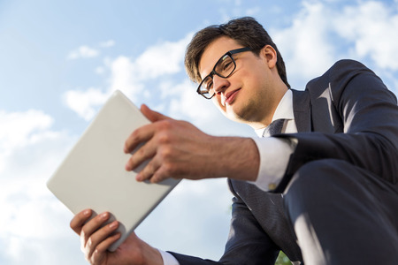 Happy young businessman in suit using tablet outside on sky background Stock Photo