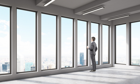 large office: Man in empty office room looking at big city through large window. Concept of thoughtfullness. 3D render.