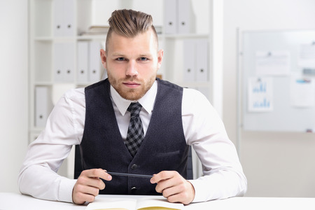 decission: Portrait of young businessman thinking about something serious and looking at camera. Concept of office work and difficult decission Stock Photo