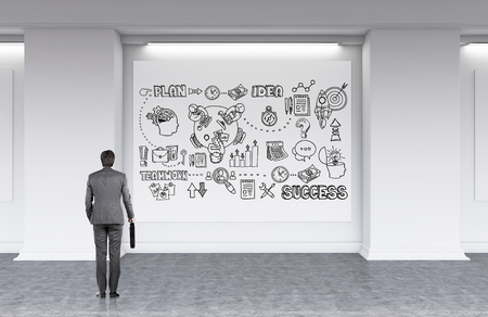 looking for: Businessman in gray clothes with suitcase is looking at whiteboard with abstract sketches on it developing new strategy for his company. Concept of business planning. 3d rendering
