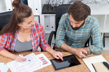 schemes: Teamwork of young man and young woman. She is pointing at tablet and drawing schemes. He is looking at screen holding smartphone. Concept of working together
