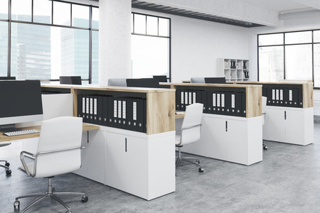 office computer: Side view of coworking office interior with computer monitors on several workplaces, cabinets with document folders and windows with city view. Mock up, 3D Rendering Stock Photo