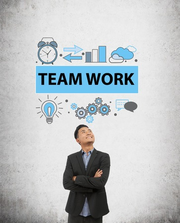 teambuilding: Businessman in dark suit is standing in front of concrete wall with team work sketch on it looking up and smiling. Concept of teambuilding in modern company Stock Photo