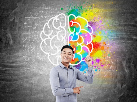 advocate symbol: Businessman in shirt standing in front of chalkboard with colorful brain sketch and equations pictured on it pointing upwards and smiling broadly. Concept of finding new thing in science.