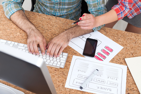 top veiw: Man and woman working together at cork table in modern office. Concept of cooperation in business Stock Photo