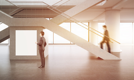 climbing stairs: Building interior. One businessman is climbing stairs while his colleague is looking at large poster on wall under it. Concept of busy office. 3d rendering. Mock up. Toned image. Stock Photo