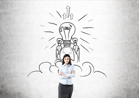 implementing: Brunette businesswoman standing in front of concrete wall with light bulb spaceship sketched on it. Concept of finding good idea and implementing it to life.