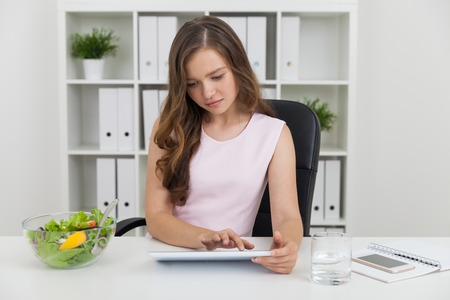 Woman using  her tablet. Bowl with salad and glass of water standing beside her at table. Bookcase with binders at background. Concept of lunch at working place. Stock Photo