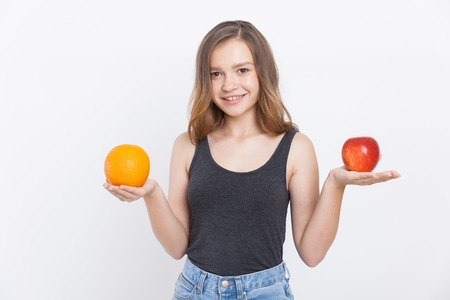 importance: Girl with orange and apple in her hands smiling to camera. Concept of right food choices and their importance for health. Portrait. Isolated.