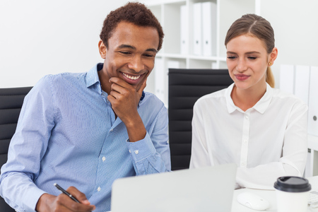 african solidarity: Man and woman in casual clothes smiling and looking at computer screen. Concept of working together