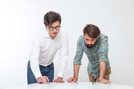 Man and his coworker looking at blueprints on white desk. Concept of engineering work