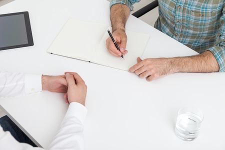 teambuilding: Two men working together at office desk. Concept of teambuilding. Top view.
