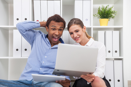 team communication: Man and woman looking at laptop screen and smiling. Concept of having fun during lunch break