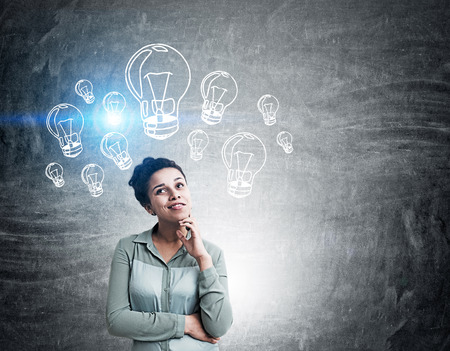 original idea: Woman in shirt is standing in front of chalboard with light bulb sketches on it thinking about new way to solve difficult problem. Concept of original idea in business. Toned image