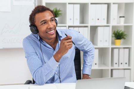 lunch hour: Black man listening to music in headphones sitting at his workplace in office. Concept of free time during lunch hour Stock Photo