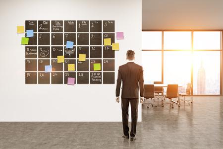 tra l'Ufficio. Imprenditore in piedi in camera guardando grande calendario sul muro. Concetto di buona programmazione. rendering 3d. Viraggio