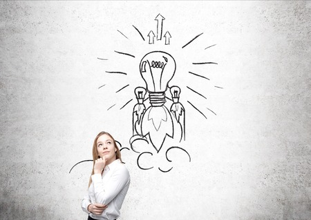 finding your way: Woman with blond hair standing in front of concrete wall with light bulb rocket flying up drawing on it. Concept of inventing new and original thing and finding your way in business.