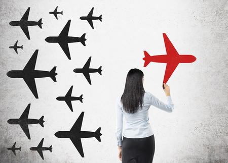 original idea: Woman in formal suit is drawing bright red airplane on concrete wall. There are drawings of black planes on the wall. Concept of original idea. Stock Photo