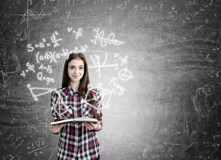 exact: Young girl with long hair holding book and smiling standing near blackboard with formulas on it. Concept of exact sciences studying