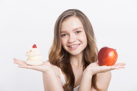 chose: Girl holding apple and cupcake and smiling to camera. Concept of various food alternatives