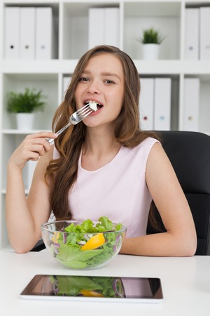 Woman eating salad from glass bowl at her working place. Tablet computer lies on table. Bookcase with binders at background. Concept of vegetarian lunch. Stock Photo
