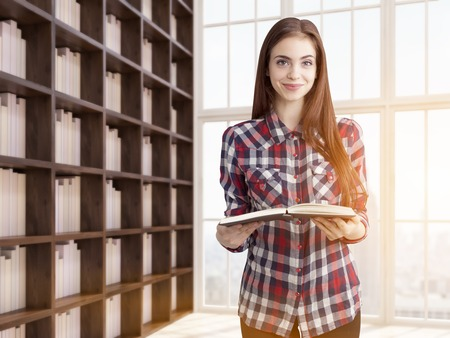 pastime: Young woman in her library holding book and smiling beside tall bookshelf. Concept of studying and good pastime. 3d rendering. Toned image. Close up Stock Photo