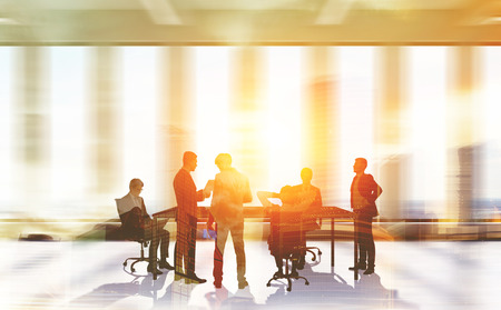 Businessmen negotiating in large sunlit room. Concept of corporate work. Toned image Stock Photo