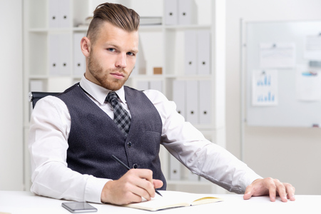 Young businessman sitting in armchair at desk writing something in his notebook and looking at camera. Concept of corporate business Stock Photo