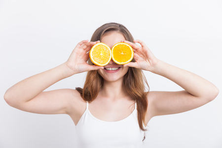 Girl holding halves of oranges near her eyes. Concept  of playfulness
