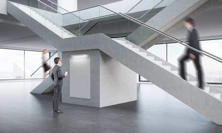 stairs interior: Office interior. One businessman is looking at large poster while man and woman are climbing stairs above him. 3d rendering. Mock up