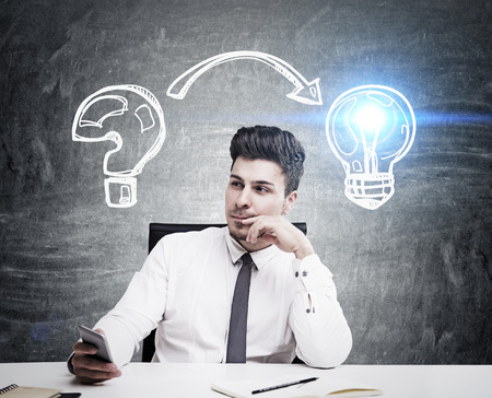 original idea: Man in tie and shirt sitting at table against blackboard background and looking for problem solution. Concept of original idea. Toned image Stock Photo